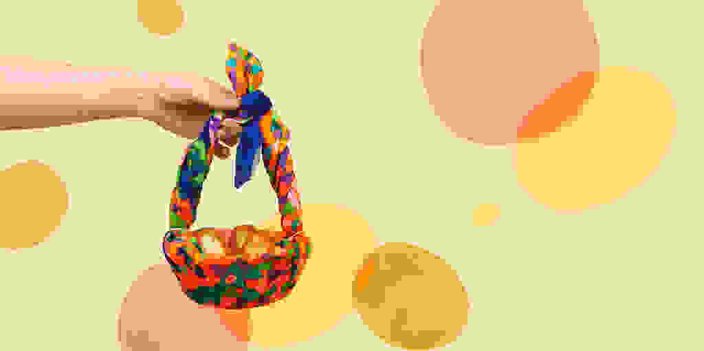 A person holding an Easter Basket wrapped in a knot-wrap with Golden Egg Bath Bombs inside
