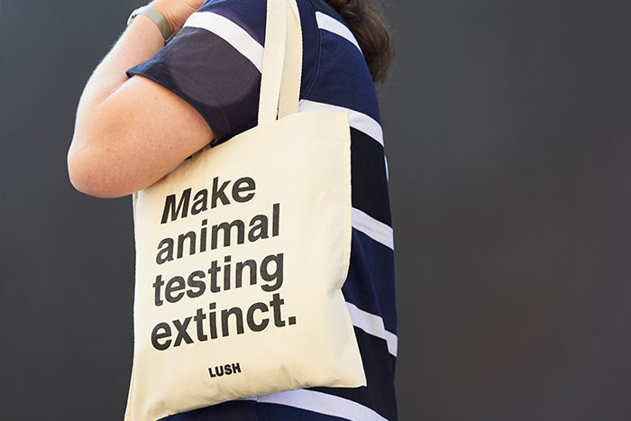 "A person carries a Lush tote with the quote ""Make animal testing extinct""."