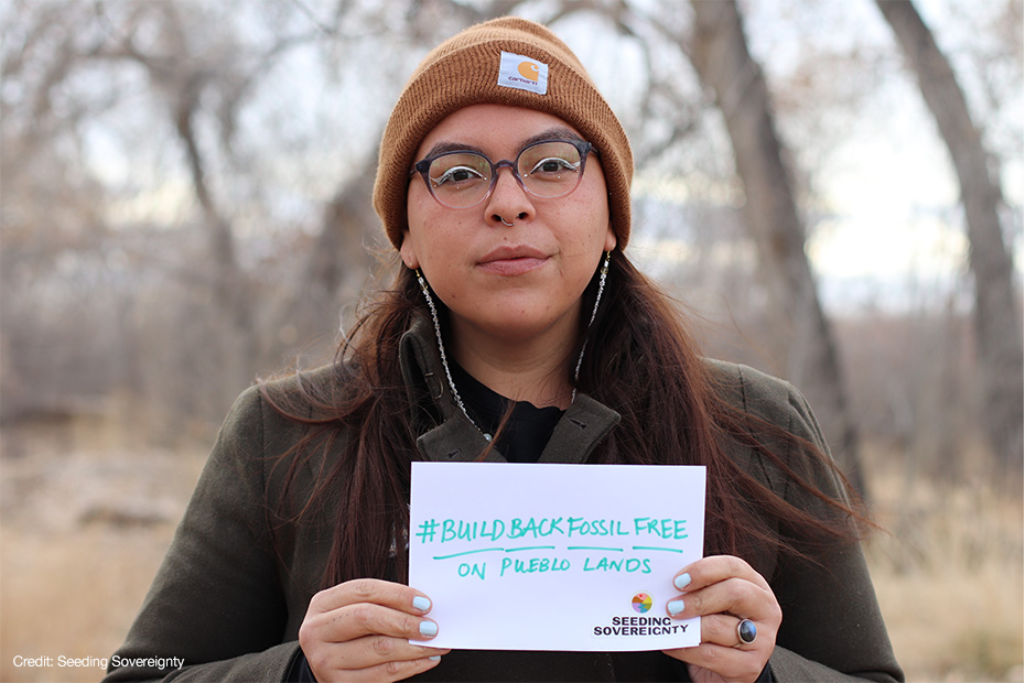 A person stands facing the camera holding a sign that reads hashtag build back fossil free on pueblo lands.