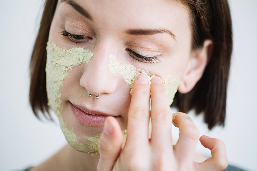 A woman applies Brazened Honey Fresh Face Mask to her face