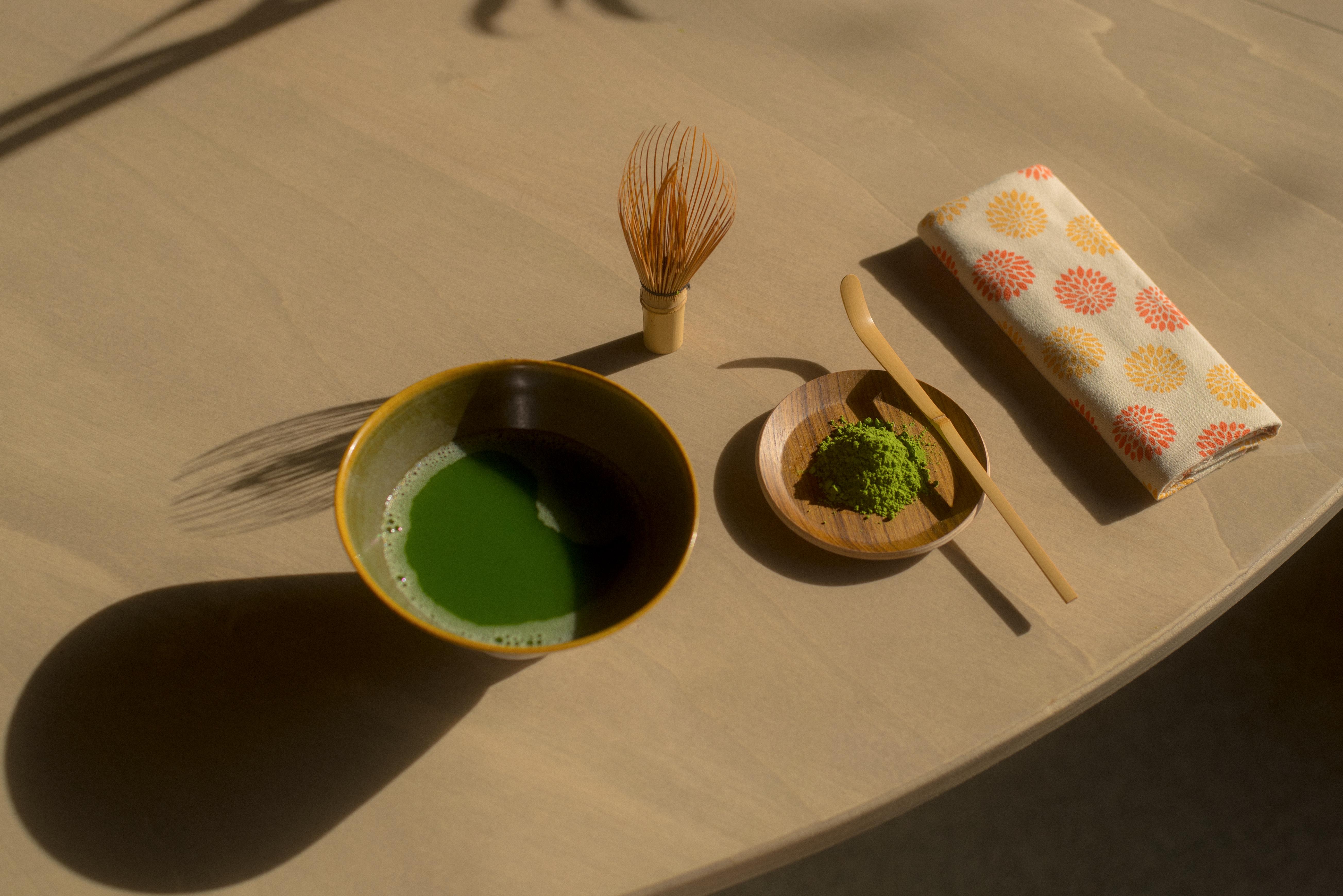 A matcha tea setting showcases a bowl, dried tea and napkin sitting on a table.