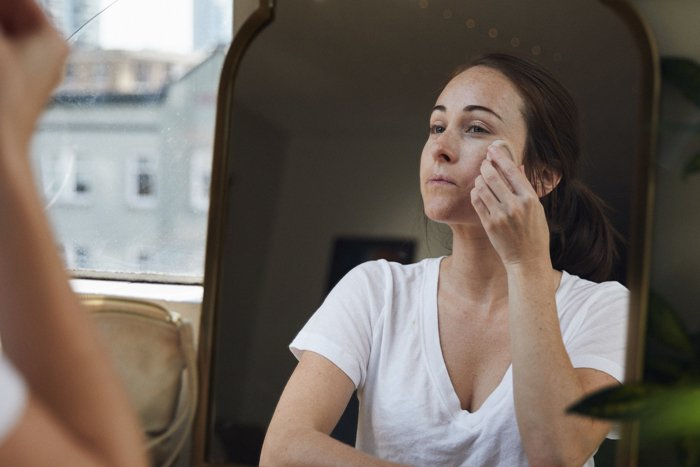 A person rubs a packaging-free Full Of Grace Facial Serum into their skin.