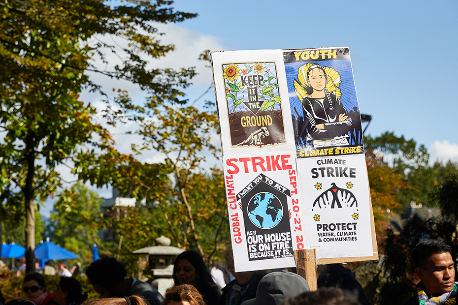 A group of people stand against a backdrop of trees and blue skies with a sign containing various slogans about the climate strike.