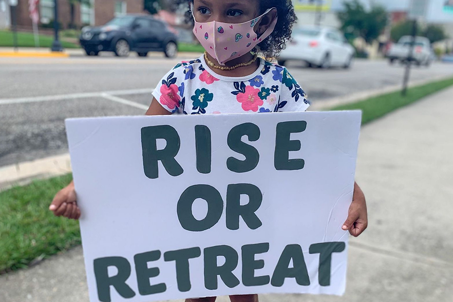 A small child standing outside on a sidewalk is wearing a face mask and holding a sign that reads rise or retreat.