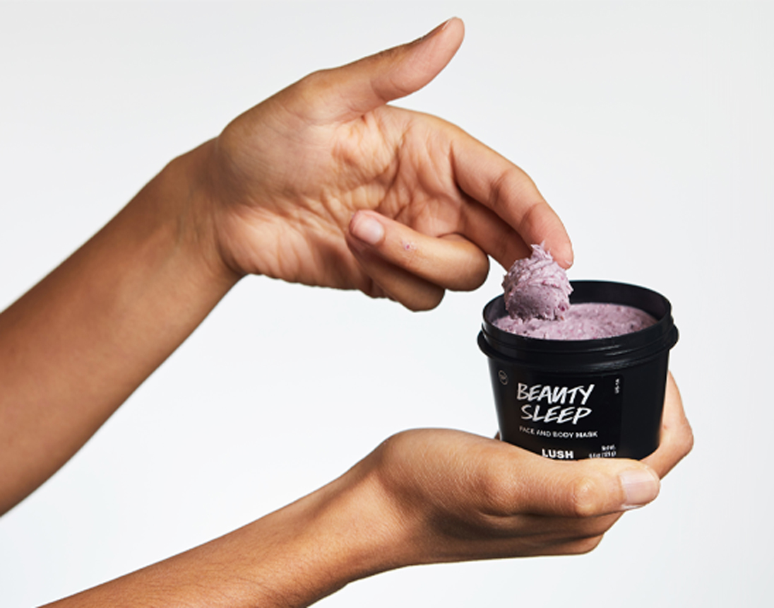 A person's hands holding Beauty Sleep and grabbing product from the pot over white background.