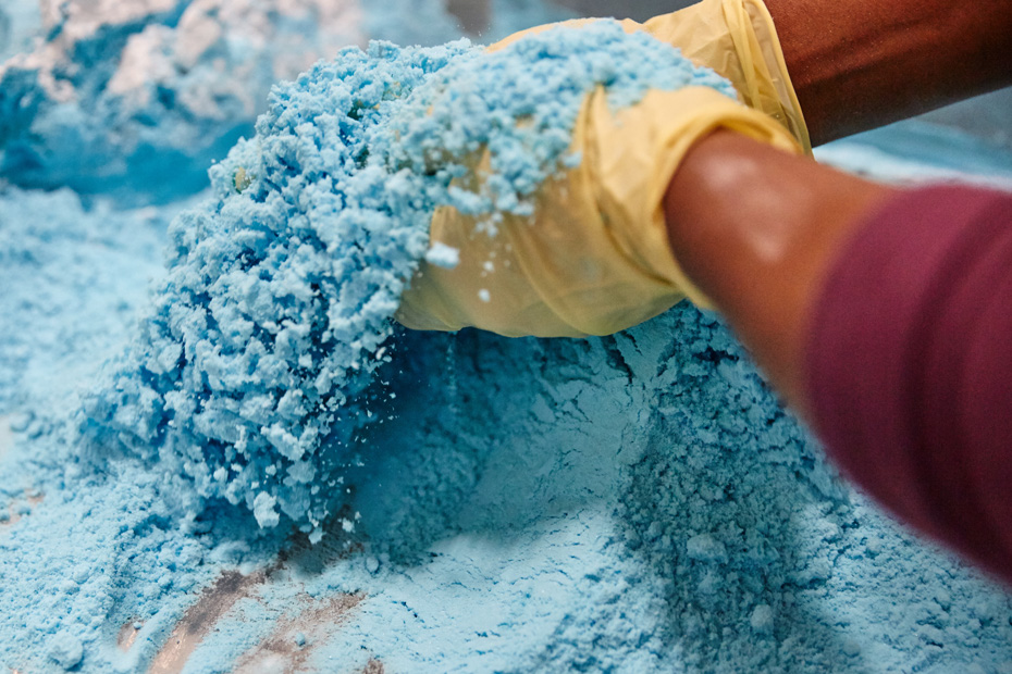 Gloved hands can be seen manipulating a blue powdery mix.