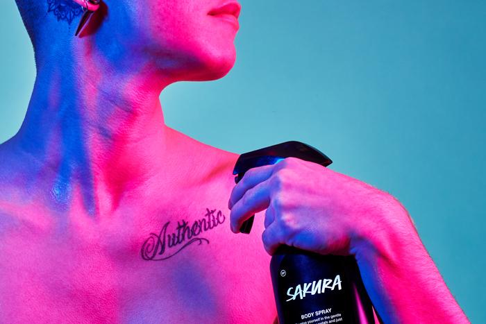 A person spritzes Sakura Body Spray onto their collarbone.