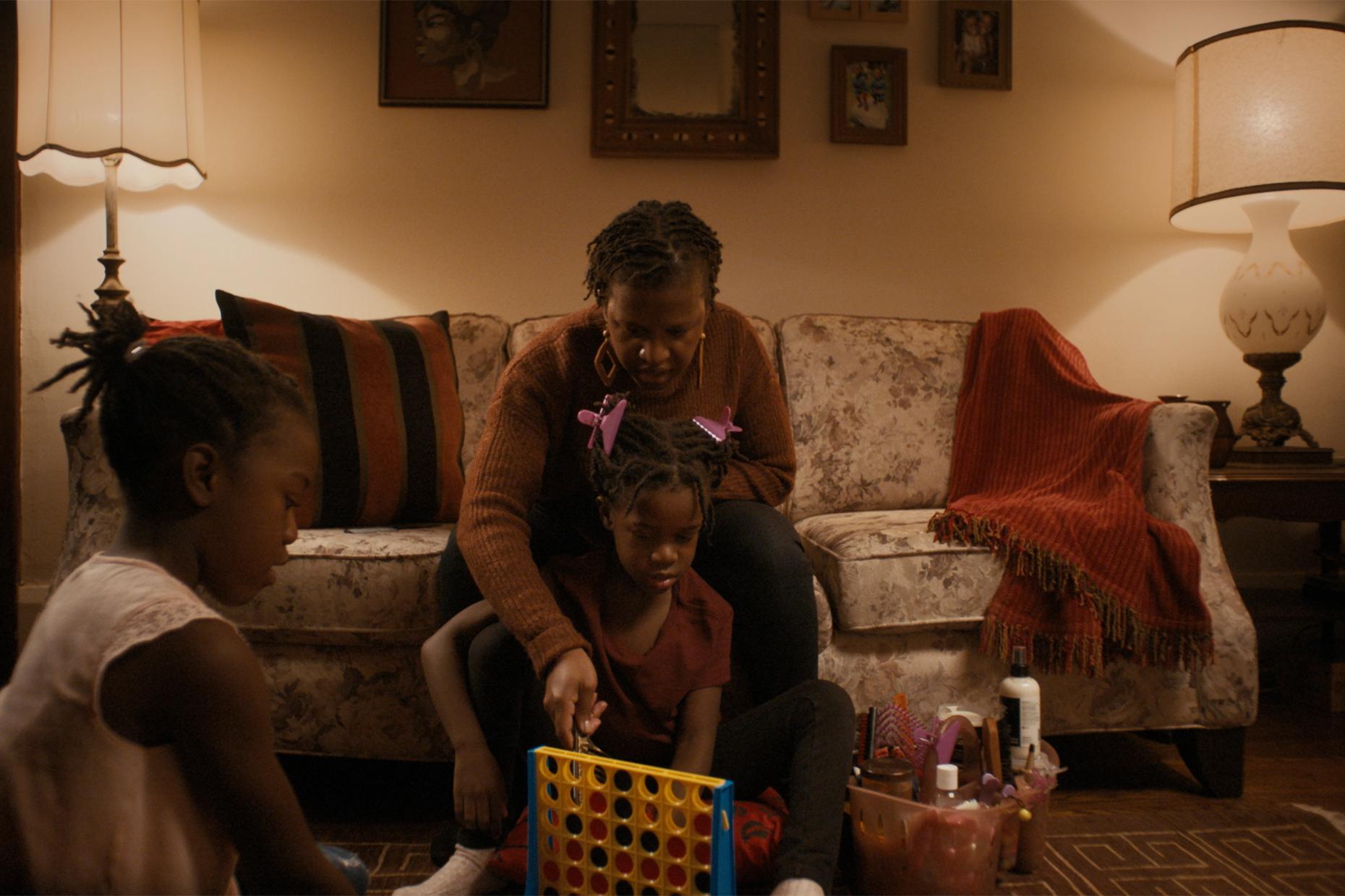 A person sitting in a living room, braiding a kid's hair.