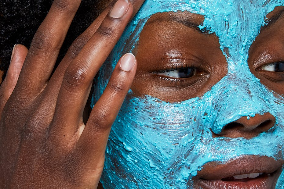 A close up on someone as they apply the bright blue Don't Look At Me Fresh Face Mask over their entire face.