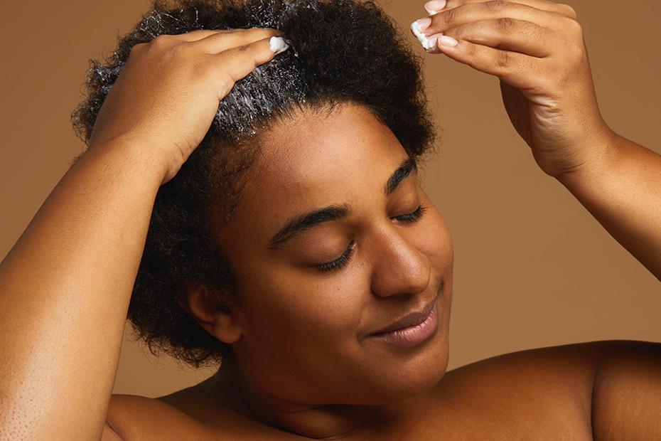 A person applies Roots Hair Treatment to their hair.