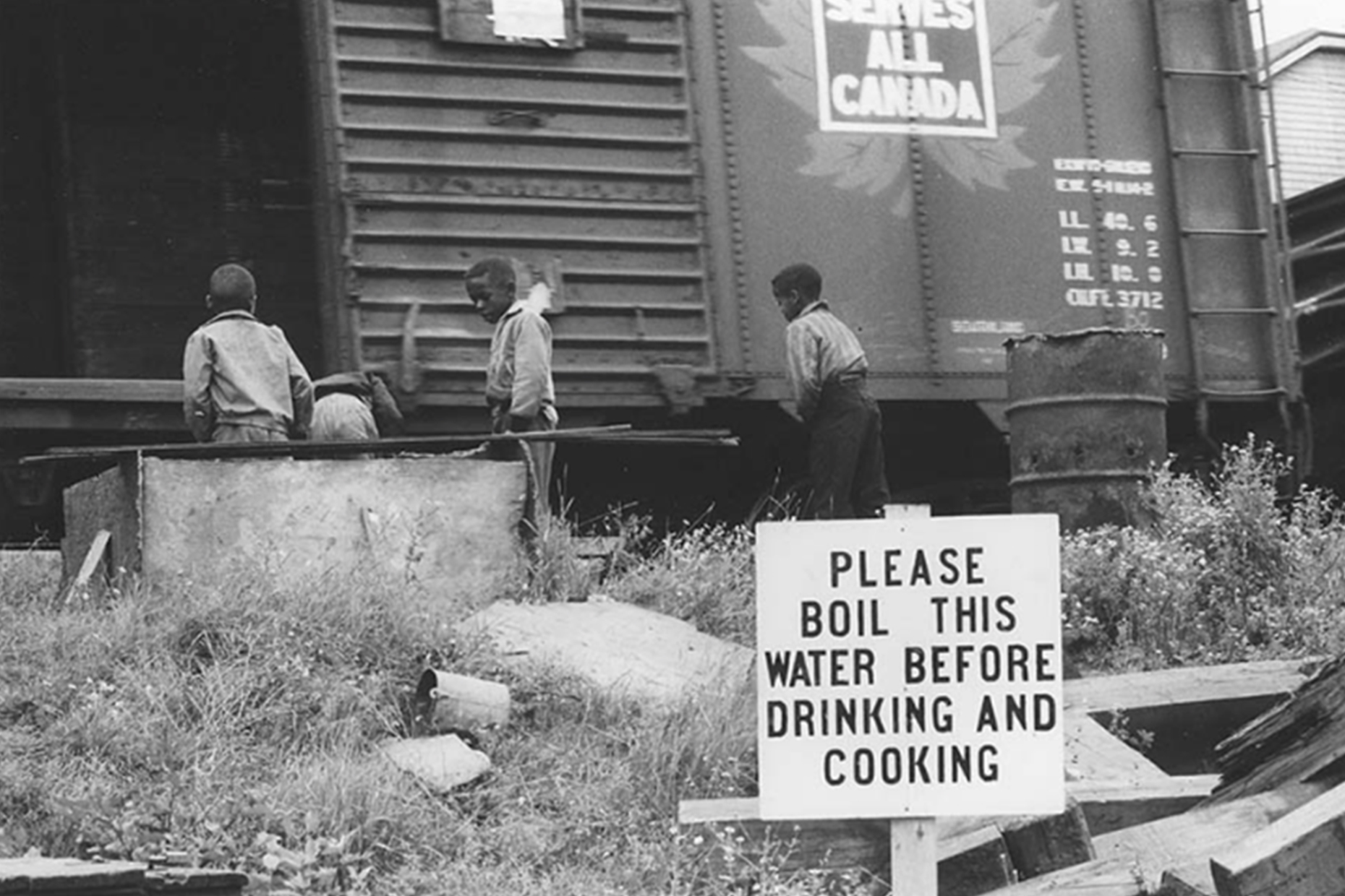 A black and white photo of three children standing near a train with a sign that reads please boil this water before drinking and cooking.