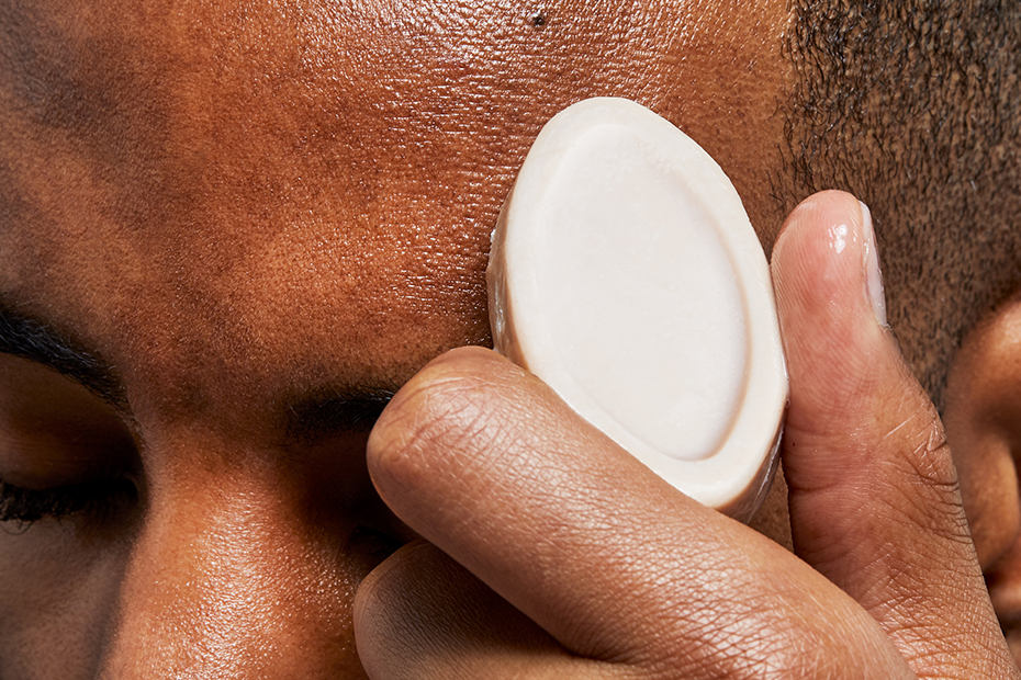 A close-up of a person's forehead, we see as their hand holds a solid lotion against their head.