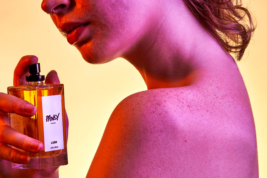 A person spritzes Pansy Perfume onto their shoulder.