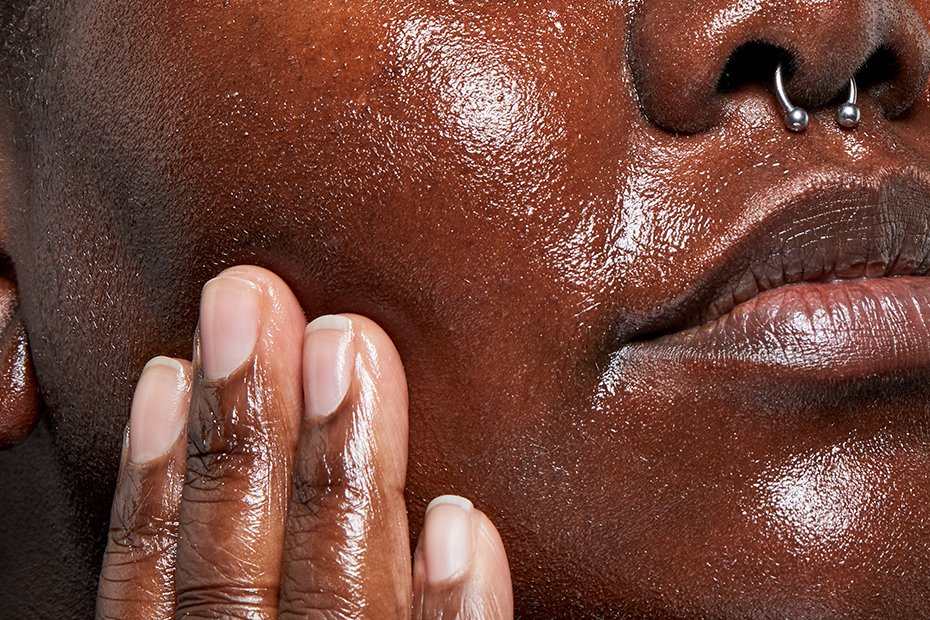 A closeup of a person's face as they rub cleanser onto their cheek.