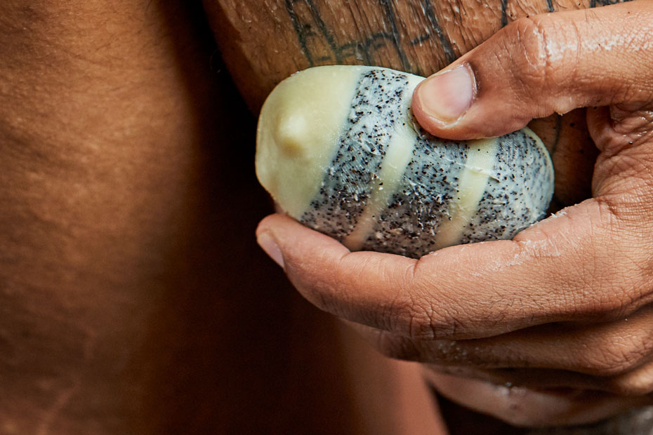 A close up of a person rubbing Scrubee onto wet skin.