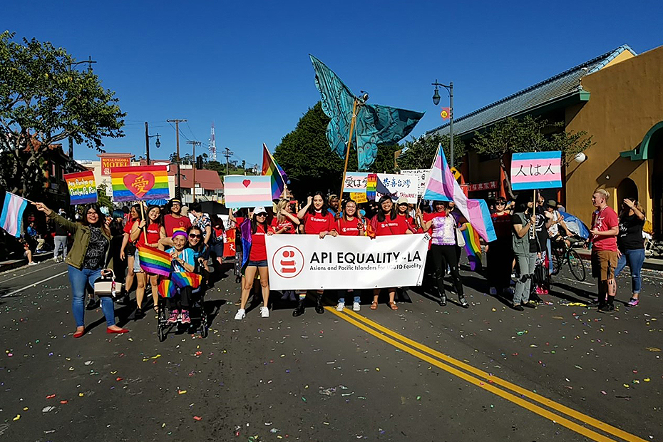 A group of people stand on a street, holding pride and trans flags, and a banner that reads API Equality LA.