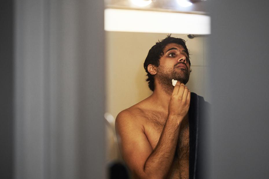 Kultar applying Dirty Beard Oil to his beard.
