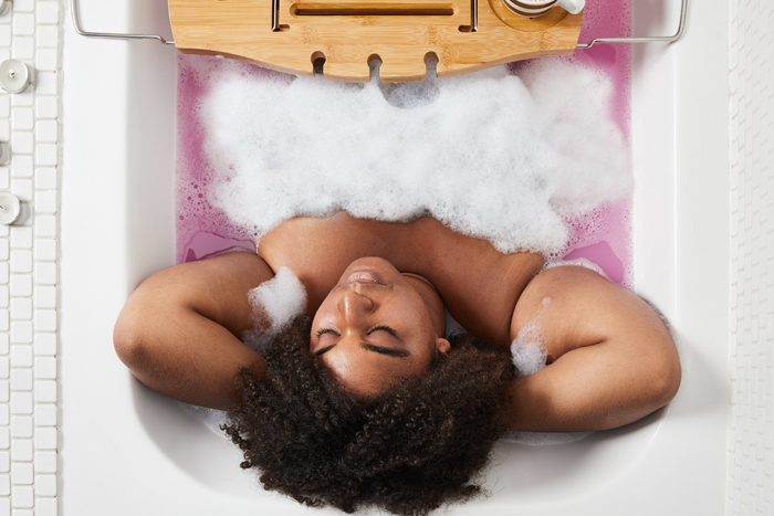 Woman relaxing in the bath tub with The Comforter Bubble Bar.