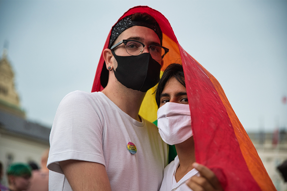 Two people wearing masks hold each other facing the camera with a rainbow flagged draped over them.