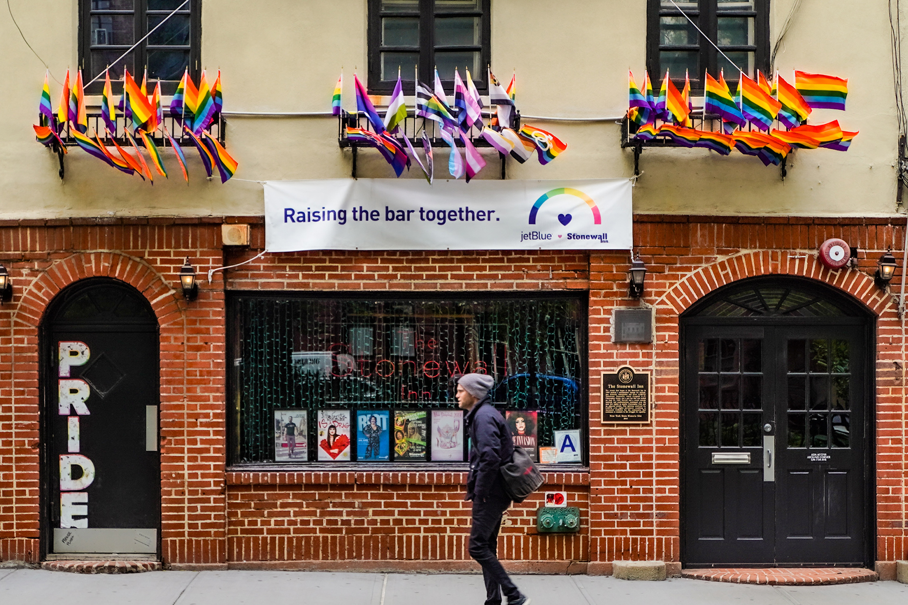 A person walking in front of the Stonewall Inn on Christopher Street.