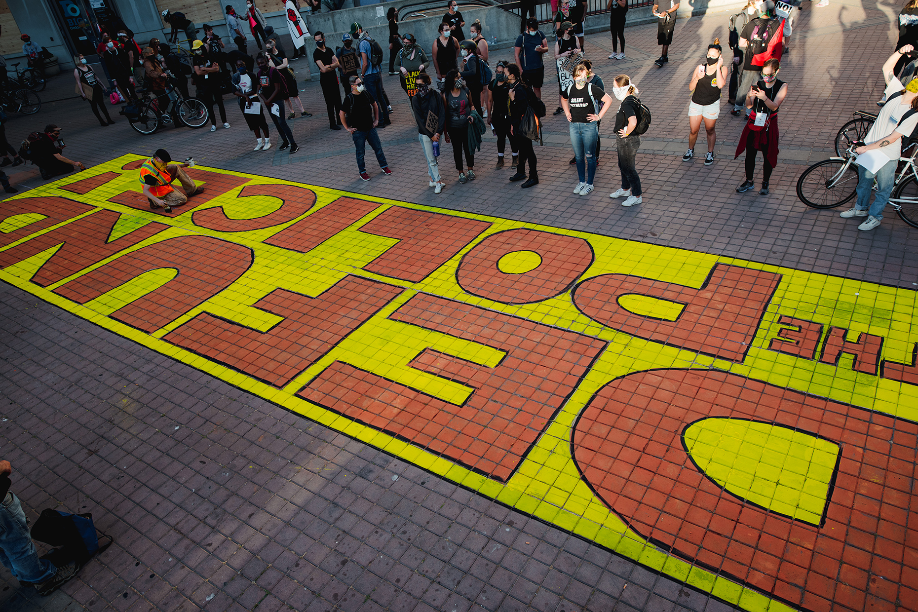Protestors painting a sign in the street that says 'Defund the police'. Photo by: Survival Media